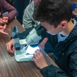 Student from Little Current Public School looking through a microscope
