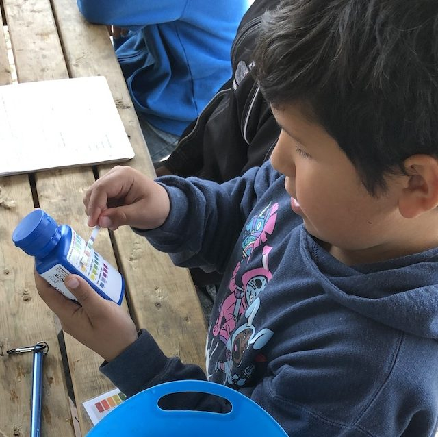 Student from Wahgoshig First Nation checking water sample results